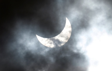 Clouds obscure the moon passing in front of the sun as it approaches a full solar eclipse in the northern Australian city of Cairns